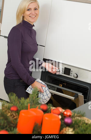 Housewife opens the oven - Housewife open the baking oven, Hausfrau öffnet den Backofen - Housewife open the baking - Stock Photo