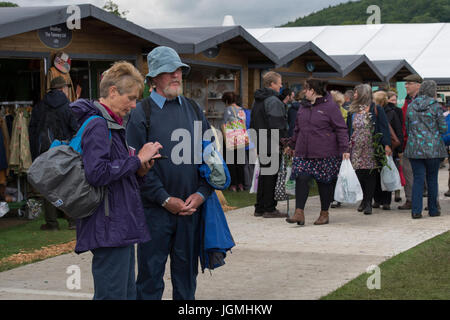 Crowd of people walking & exploring avenue of wooden retail outlets - RHS Chatsworth Flower Show showground, Chatsworth - Stock Photo