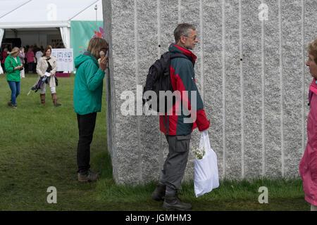 Woman looks into huge granite cube freeform garden (Antithesis of Sarcophagi) - RHS Chatsworth Flower Show, Chatsworth - Stock Photo