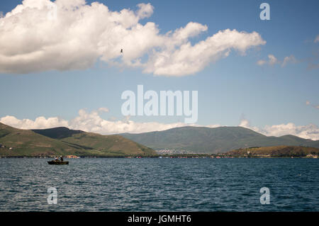 Fishing boat on Lake Sevan in Armenia with clouds and mountains. - Stock Photo