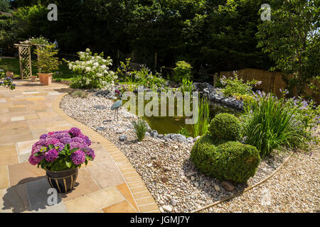 Garden patio at the edge of a pond with plant pots, topiary,hydrangeas,white moth hydrangea paniculata , - Stock Photo