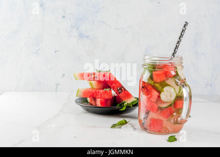 Summer drinks and cocktails. Lemonade, infused detox water with mints, fresh watermelon and cucumber. In mason jar, - Stock Photo