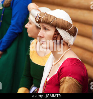 Middle ages period costume - young noble lady wearing red dress, a headgear and braids hairstyle. A woman dressed - Stock Photo