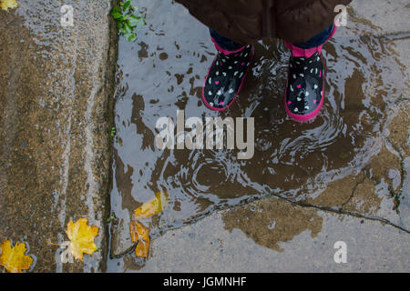 A small child stands in rain boots in a puddle in autumn. - Stock Photo