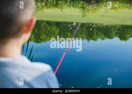 A child fishing at a pond in a rural area. - Stock Photo