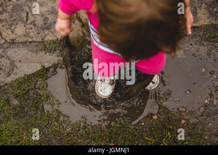 A 2-year old girl, looking down at ground and mud puddle, splashes in a mud puddle, making a mess of her clothes - Stock Photo