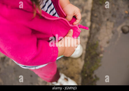 A toddler zipping her jacket hands only. - Stock Photo