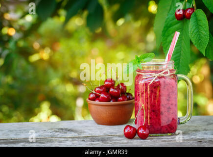 cherry smoothie in mason jar with sunshine garden on the background. Healthy summer drink concept. Berry cocktail - Stock Photo