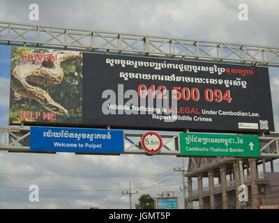 Poipet Cambodia Decrepit Impoverished Town on the Thailand Border Line Billboard Across the Highway - Stock Photo