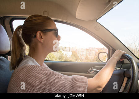 Blondie young woman driving a car - Stock Photo