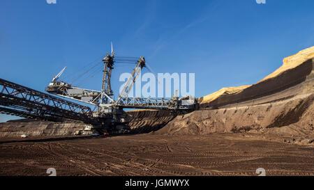 Bucket-wheel excavator mining in a brown coal open pit mine. - Stock Photo