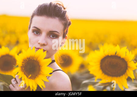 Beautiful natural young woman at sunflower field in summer sunset - Stock Photo
