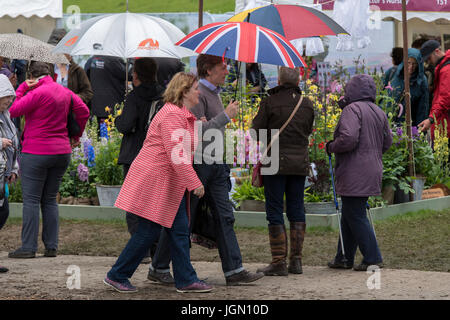 People under umbrellas, explore displays of plants - Plant Village, RHS Chatsworth Flower Show showground, Chatsworth - Stock Photo