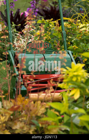 Plants, shrubs and old push lawnmower in beautiful display garden - RHS Chatsworth Flower Show showground, Chatsworth - Stock Photo