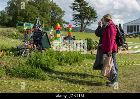 Two people viewing theatrical, symbolic & surreal Pic 'n' Mix show garden at RHS Chatsworth Flower Show, Chatsworth - Stock Photo
