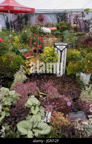 Plants, shrubs, lawnmower & boundary post in BBC display garden - RHS Chatsworth Flower Show showground, Chatsworth - Stock Photo
