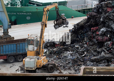 Yellow crane getting scraps cars from a scrap mountain at a sea port (Pasajes, Guipuzcoa, Spain). - Stock Photo