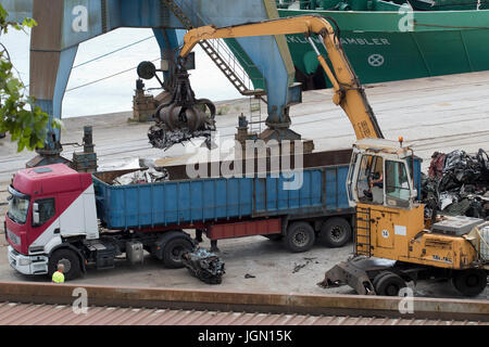 Loading scaps cars in a articulated lorry with the help of a crane, in a sea port (Pasajes, Guipuzcoa, Spain). - Stock Photo