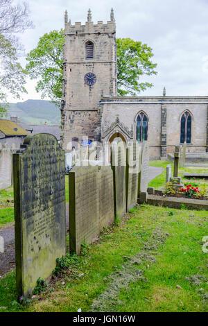 The parish church and stone headstones in Castleton, Peak District, Derbyshire, England, UK - Stock Photo