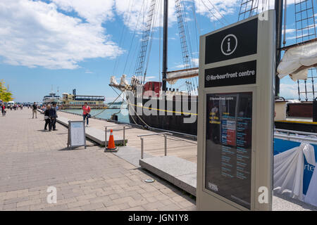 Toronto, Canada - 26 June 2017: The Harbourfront Centre sign with an old sailship in the background - Stock Photo