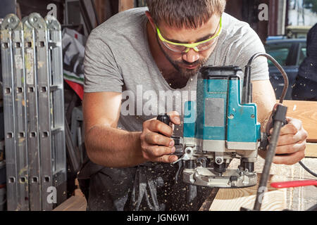 A young brunette man wearing safety goggles and a gray T-shirt carpenter builder pre-works the edges of the wooden - Stock Photo