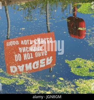 Danger do not drag anchor 11000 volt cable sign and life belt reflected in Exeter Canal - Stock Photo