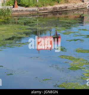Danger do not drag anchor 11000 volt cable sign reflected in Exeter Canal - Stock Photo