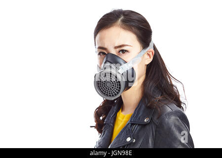 young asian woman in black leather wearing gas mask staring at camera, isolated on white background. - Stock Photo