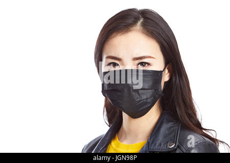 young asian woman wearing black mask staring at camera, isolated on white background. - Stock Photo