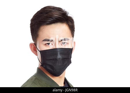 young asian man wearing black mask staring at camera, isolated on white background. - Stock Photo