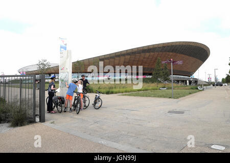 Family with bicycles outside the Queen Elizabeth Olympic Park Velodrome cycling building in Stratford, Newham East - Stock Photo