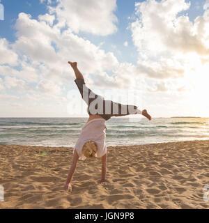 Free Happy Woman Turning Cartwheel Enjoying Sunset on Sandy Beach. - Stock Photo