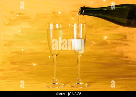 Sparkling wine poured into glasses on golden background - Stock Photo