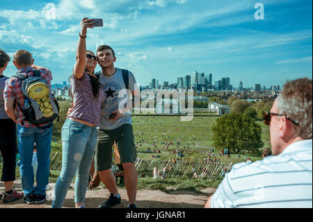 Young couple is taking a selfie with Canary wharf in the background. - Stock Photo