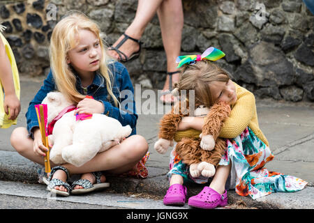 Two young Caucasian children, girls, 5-6 years old, sitting on kerb of pavement, watching something (unseen) clutching - Stock Photo