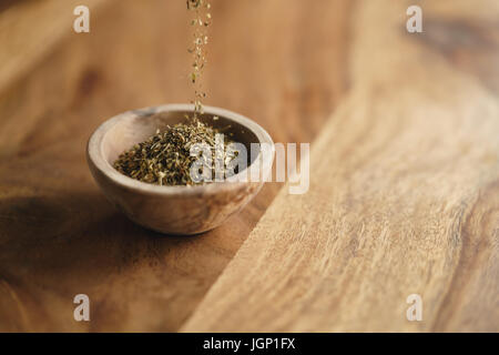 dried provence herb mix falling in wood bowl for seasoning on table - Stock Photo