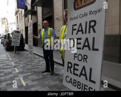 Taxi drivers protest for a fairer deal outside the Cafe Royal in London - Stock Photo