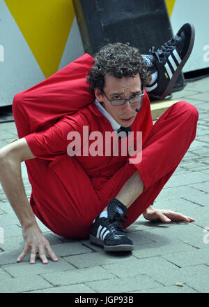 Combining comedy, contortion and stunts, Jonathan Burns from the USA performs at the 18th World Buskers Festival - Stock Photo