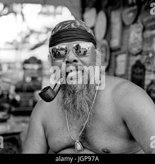 Black and white photography portrait of a pipe smoking shirtless Asian man. Thailand Southeast Asia - Stock Photo