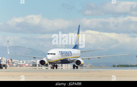 Aircraft Boeing 737 Ryanair low cost airline, is arriving to the passengers terminal, after it has landed in Madrid - Stock Photo