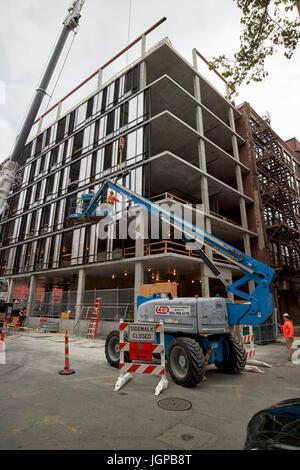 cherry picker elevated platform guiding building panels on construction site Boston USA - Stock Photo