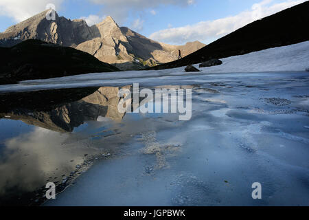 Woman silhouette hiking by a frozen lake with a scenic view over the mountains, Passo Agnello, Italy. - Stock Photo