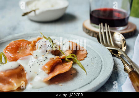 Carrot  pasta stuffed with cheese and vegetables, with béchamel sauce, set table. - Stock Photo