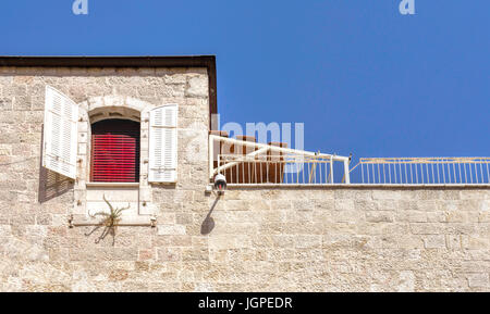 Red blinds, white shutters and blue sky, a colorful and scenic impression in the Armenian Quarter of Jerusalem, - Stock Photo