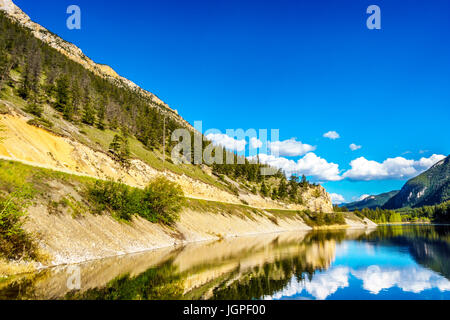 Blue sky, trees and mountains reflecting in the smooth surface on the crystal clear water of Crown Lake, along Highway - Stock Photo