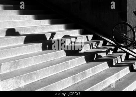 Broken shadow of a person and his bike going down the pedestrian bicycle stairway using a wheeling ramp - Stock Photo