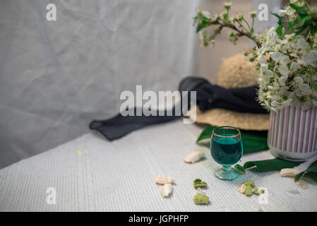 A glass of absinthe on a white background with a sheet of monsters and a straw hat - Stock Photo