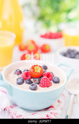 A bowl with homemade oatmeal porridge with fresh fruit on a rustic outdoor table. - Stock Photo