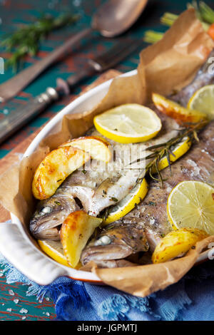 An oven roasted trout in a casserole on a rustic table. With carrots and potatoes on the side. - Stock Photo