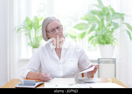 Senior woman at home with a calculator and lots of bills and receipts, filling out the printed forms of the annual - Stock Photo